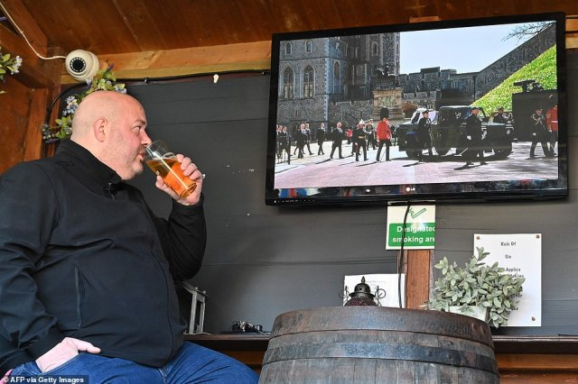 A man drinks his pint watching a live broadcast from Windsor of the funeral for Prince Philip, Duke of Edinburgh at The Duke of Edinburgh pub, in Winkfield, west of London