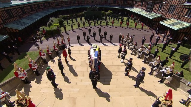 Pallbearers carry the lead-lined coffin up the steps into the chapel watched by dozens of soldiers