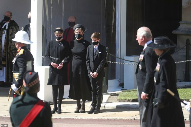 Sophie, the Countess of Wessex, center, Lady Louise Windsor, and James, Viscount Severn watch the procession, as Prince Charles and Princess Anne walk past, from the Galilee Porch of St George's Chapel
