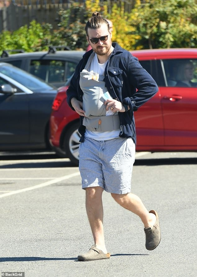 Doting dad: Matt, 32, cradled their son in a light grey baby carrier for the sunny stroll