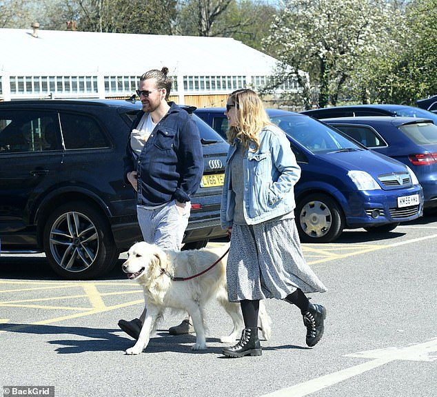 All together: Sophie held onto their dog Buddy's red lead as they crossed the car park