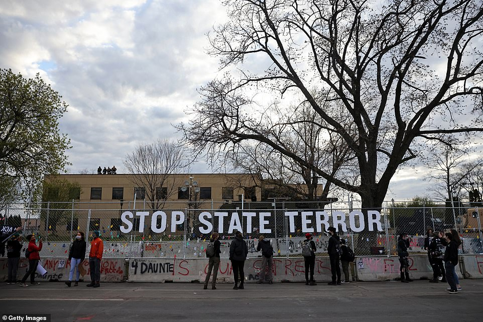 Police officers stand guard on a roof as demonstrators gather beside a sign reading 'Stop State Terror'