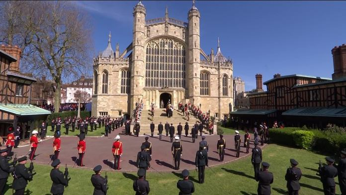 The royal family stand at the bottom of the steps of St George's Chapel as the coffin is carried into the church