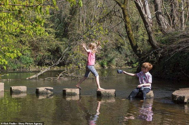 Ellie Argent, aged 6 and Dexter Argent, aged 8, play on the stepping stones as they enjoy a sunny day in Box Hill