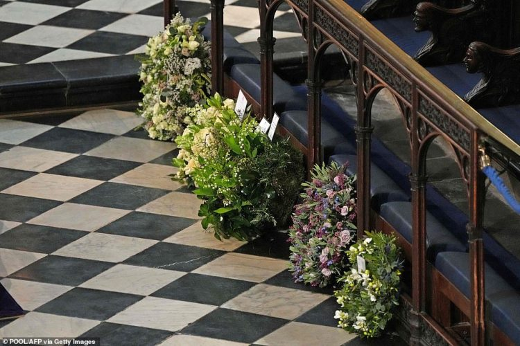 Meghan and Harry personally chose the locally-sourced flowers for their wreath (second from right) - including Acanthus mollis and Eryngium. Pictured: Wreaths from members of the royal family lie against the pews during the funeral