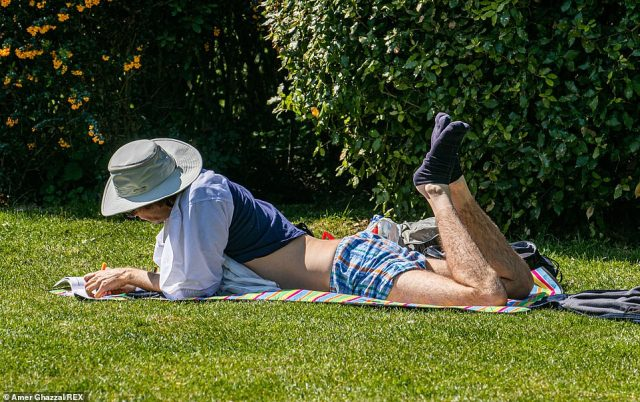 A person sunbathes on the grass at Regent's Park in London as the Met Office predicts warm temperatures throughout the week