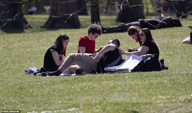 A group of people enjoy the sunshine at St James's Park, Westminster, as mercury levels begin to rise across the country today