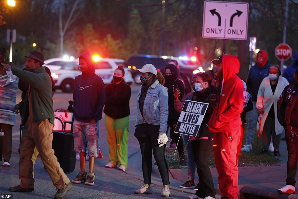A crowd gathers to protest in the neighborhood where a Columbus police officer fatally shot Bryant on Tuesday