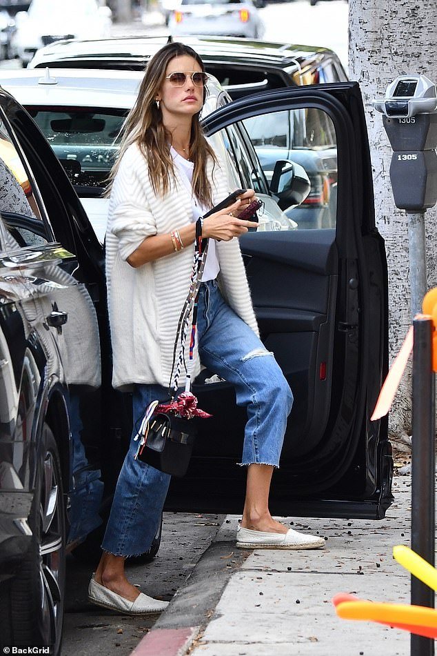 Effortless: Alessandra looked effortlessly cool in a solid white t-shirt that she tucked into the high waist of her Etica distressed denim jeans