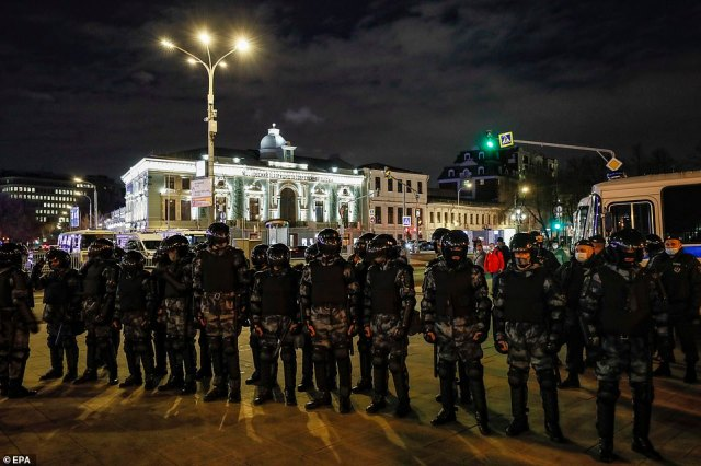 Riot police were deployed to contain protests in cities across the country last night to quell the unrest (pictured, officers block a street during a rally in Moscow)
