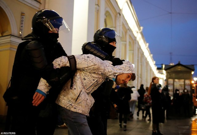 Riot police remove a protester from demonstrations against the detention of Navalny in St Petersburg last night