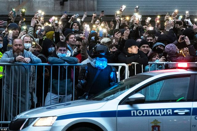 Police stood guard as protesters turned on their phone flashlights as a show of defiance during a pro-Navalny rally in Moscow