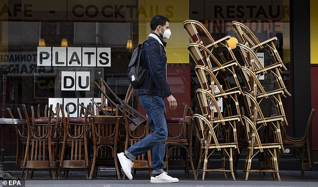 A pedestrian wearing a protective face mask walks past cafe terrace with chairs stacked outside a restaurant, in Paris