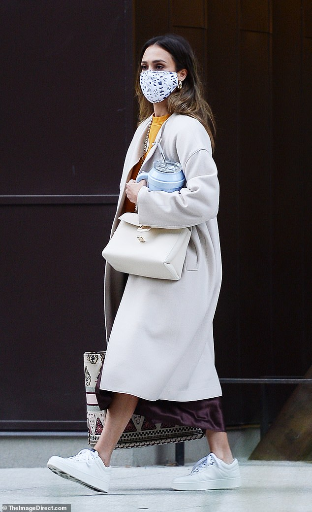 On the go: Jessica Alba was seen leaving an office building in LA on Thursday wearing a stylish white coat and white trainers along with a black and white patterned face mask