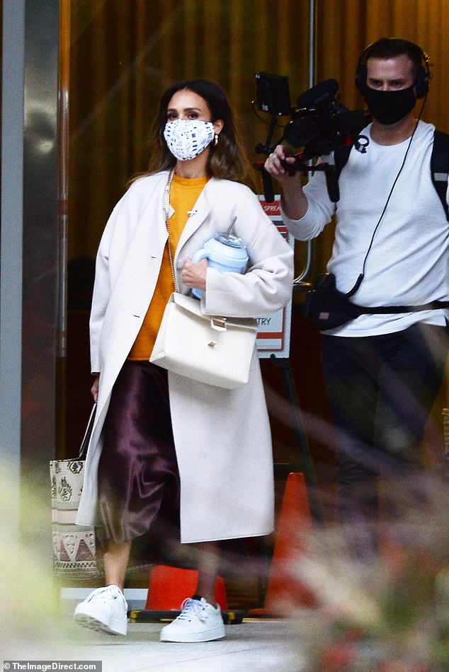 Filming: The 39-year-old wore her coat over a colorful ensemble of a sunflower yellow blouse and calf-length shiny purple skirt and she was followed out the door by a camera crew