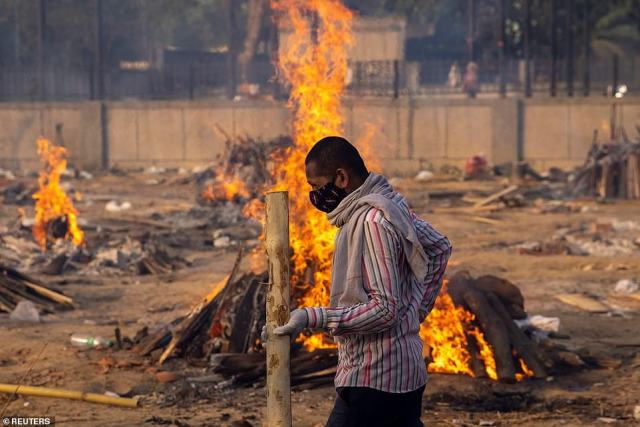 A man walks past burning funeral pyres of people in New Delhi, with 2,074 daily fatalities but experts say the true figure could be at least ten times higher