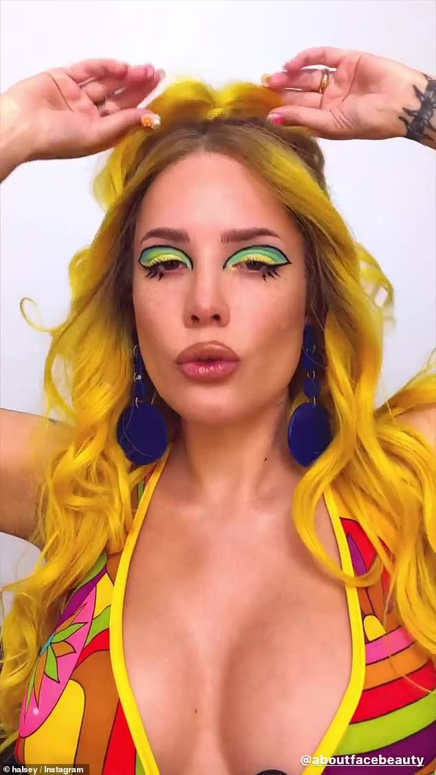 Wow:The singer, 26, wowed as she sported a yellow wig, a plunging psychedelic top and striking eyeshadow as she celebrated the release of the newest collection from her brand, 'Daytripper'