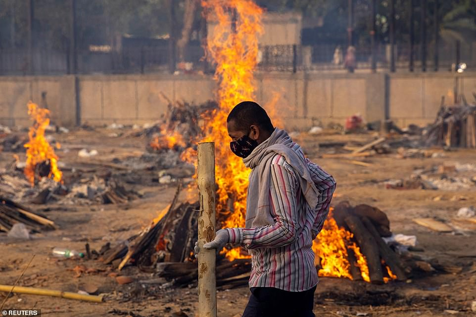 A man walks past burning funeral pyres of people, who died due to the coronavirus disease at a crematorium ground in New Delhi, India, on Thursday