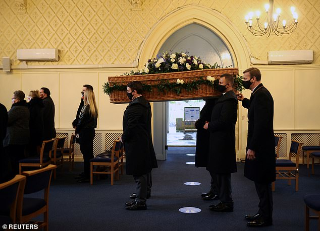 An influential committee of MPs will meet next week to pile further pressure on ministers to raise the cap of 30 mourners and allow singing again. Pictured, a funeral in east London