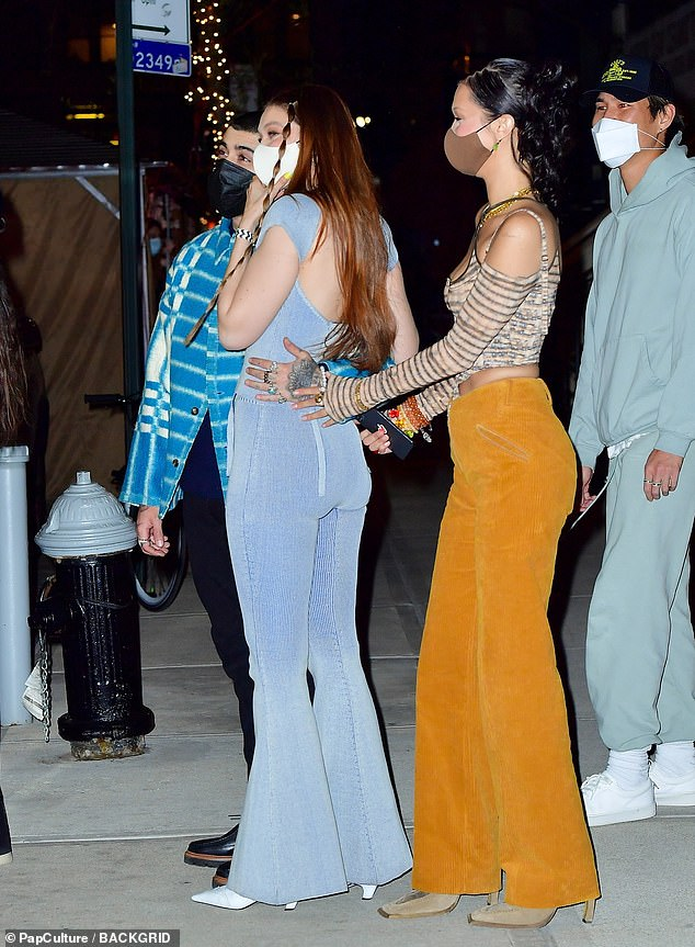 Quality time with her sis:The supermodel, 24, wowed in orange-hued corduroy slacks and a crisscross leopard-striped top with matching arm warmers