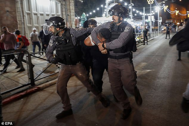 Israeli police detain a Palestinian man during clashes between the police and Palestinian protester on Saturday night
