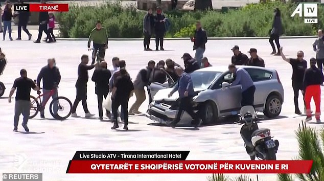 With the driver having been distracted by the brave passer-by, a crowd of pedestrians swarm around the car
