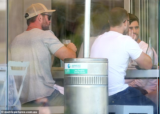 Relaxed: The men sat talking on the restaurant's balcony, with Chris keeping a low profile under a beige-coloured trucker cap and dark sunglasses