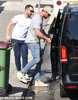 Opening doors: He ducked his head as he climbed into the back of the vehicle, with Aaron assisting him with the door