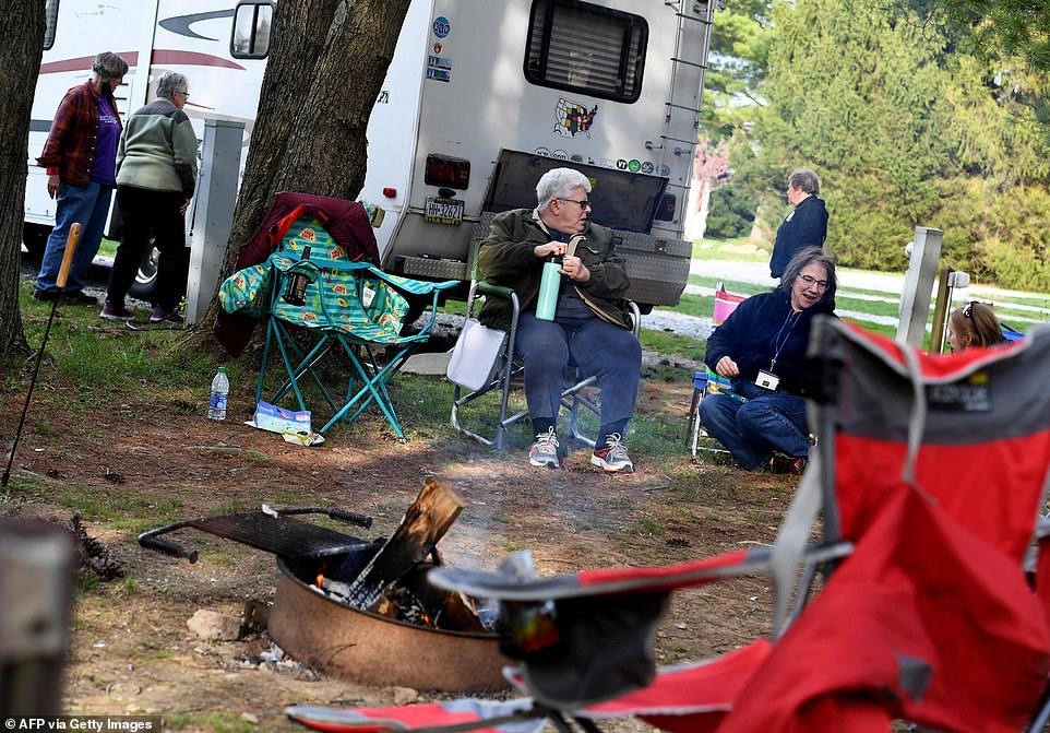 Members of the RVing Women are captured drinking together and laughing with one another while sitting around a fire, with their motorhomes surrounding them