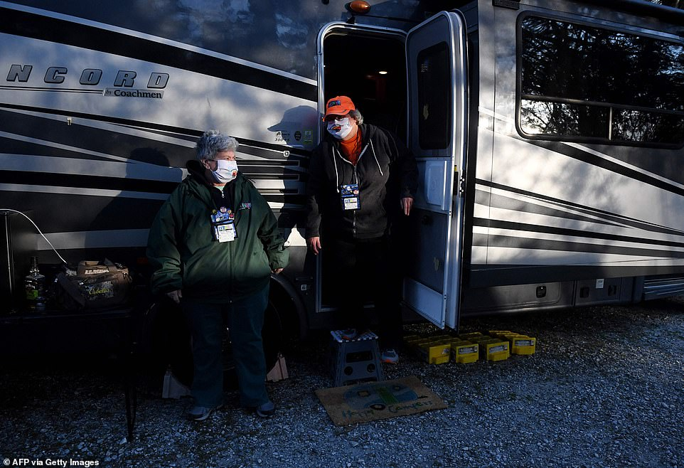 Wearing face masks to stay safe during the pandemic, Sandy Bosley (pictured left) and Kathy Healy (pictured right) leave their van to join the other members at the campsite