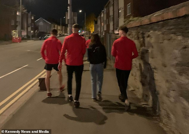 The football players (pictured helping a student home) won praise from dozens of women and were described as 'angels', while the mother of one female student 'cried with happiness' over their act of kindness