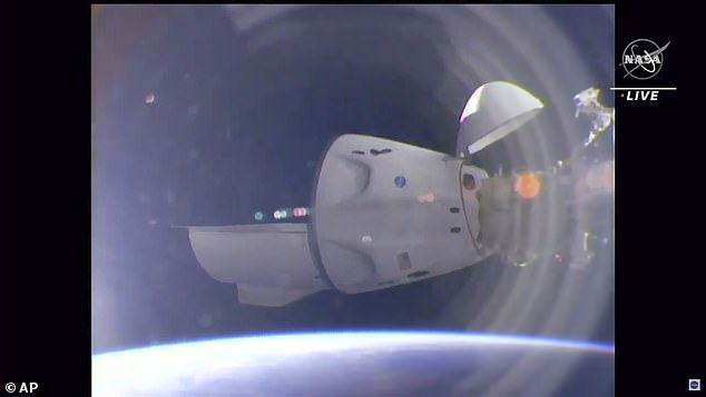The SpaceX Crew Dragon, and its four astronauts, is seen safely docked in this impressive picture from Nasa TV