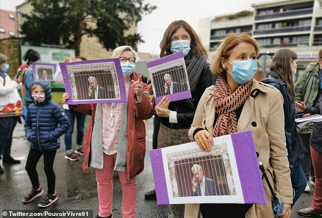 Protestors from Nous Toutes (We All) gathered with placards which pictured Tron behind bars on April 21
