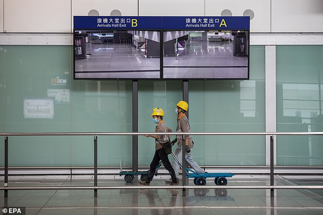 All passengers flying into Hong Kong must present a negative test within 72 hours before departing. Pictured: Workers inside the arrival hall at Hong Kong International Airport on 20 April
