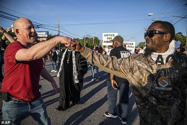 Two men fist bump amid smiles as they peacefully protest against Brown's shooting