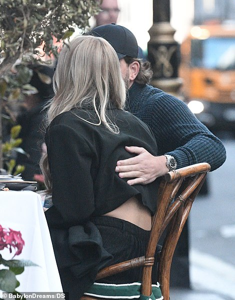 PDA: Lewis was also seen embracing Lottie at the table, inadvertently causing her black cropped jacket to ride up