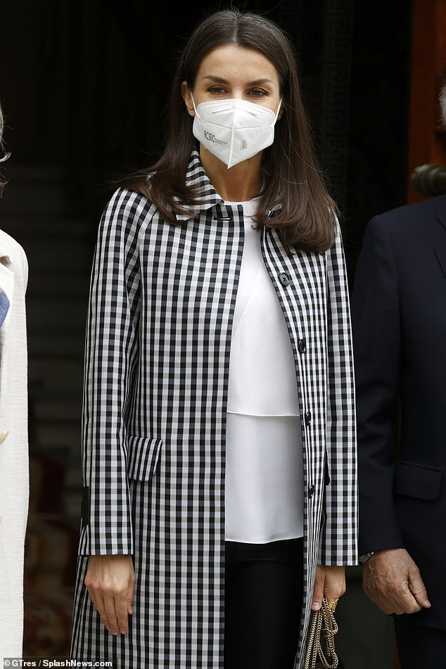 Queen Letizia of Spain proved she meant business as she arrived at a work meeting in a stylish check coat and leather leggings today (pictured)