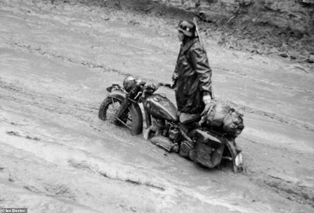 A German motorcyclist has problems with his bike, caused by the extremely muddy conditions. He is wearing the standard issue waterproof coat. It has which wool collar and two large pockets on the the front and side. On his back he is carrying a 7.92mm Kar 98k Mauser bolt-action rifle