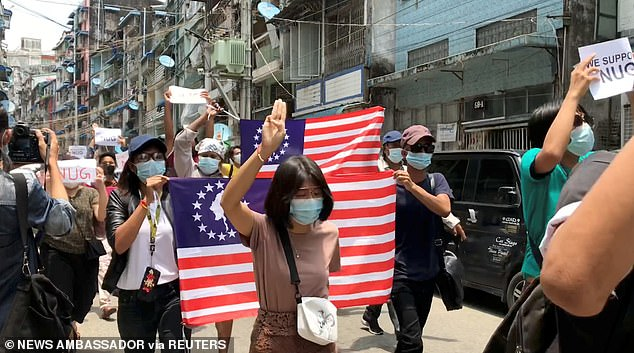The three-fingered salute has been adopted by pro-democracy protesters across Asia. Pictured: Demonstrators in Yangon on Tuesday