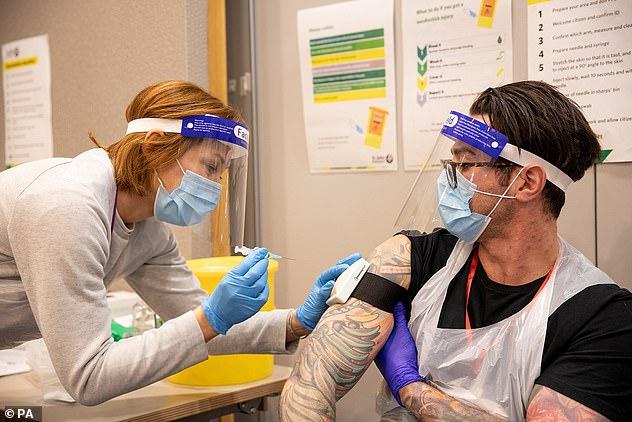 En la foto: Matt Willis es vacunado por su esposa Emma mientras trabajaba como voluntario en St John Ambulance hoy