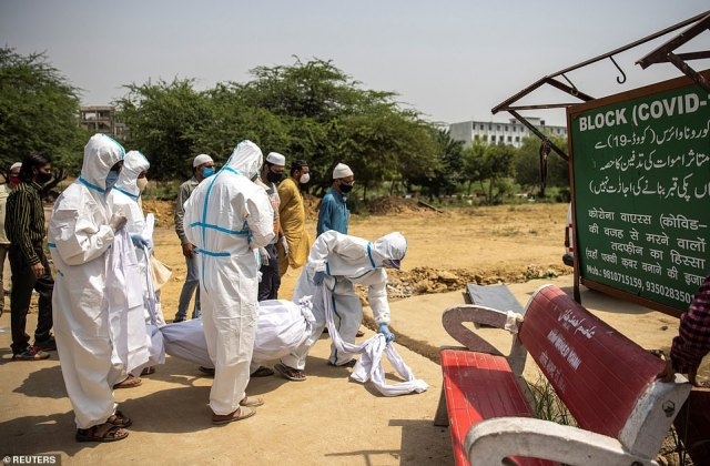 India's official Covid death toll has topped 200,000 as the country is devastated by a second wave of virus, but experts have warned the true toll could easily be double that and perhaps up to five times higher (pictured a victim is buried in Delhi)