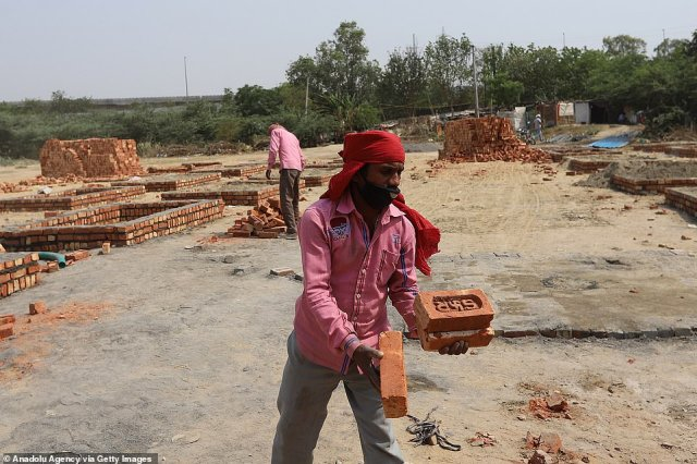 Crematorium workers in Delhi build makeshift fire pits on spare land next to a motorway in order to keep up with demand which has rocketed as the country is battered by a second wave of virus