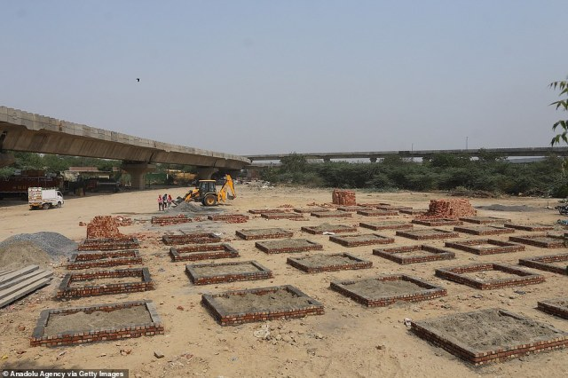 Makeshift cremation pits are constructed next to a highway in Delhi, with public parks, car parks, and gardens all repurposed to deal with a mountain of bodies caused by the Covid pandemic