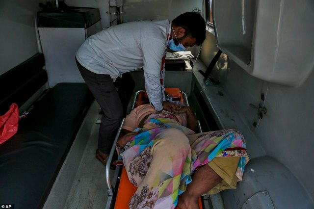 A health worker gives cardiopulmonary resuscitation (CPR) to a COVID-19 patient waiting to be attended to inside an ambulance outside a government COVID-19 hospital in Ahmedabad
