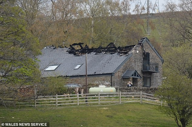 A man was found shot dead in the burning wreckage of a luxury barn conversion in south Wales