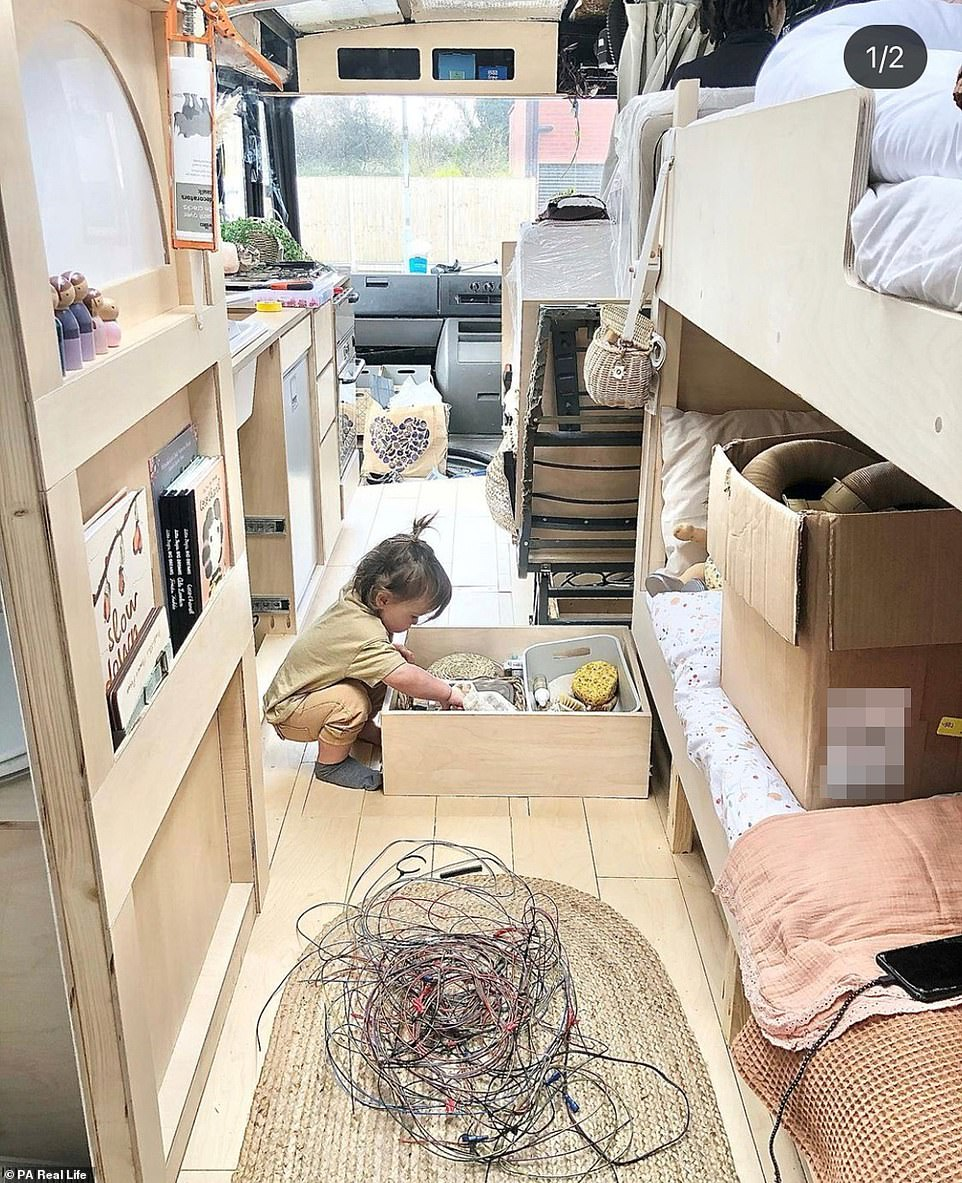 Thariea, 28, and River Paige, 27, have transformed a 2007former Bournemouth council bus bought on eBay for £8,000 into a family home for themselves and their children, Roman, eight, Arabella, six, and Nalu-River, 18 months. Pictured: Baby Nalu-River inspects his new bus home