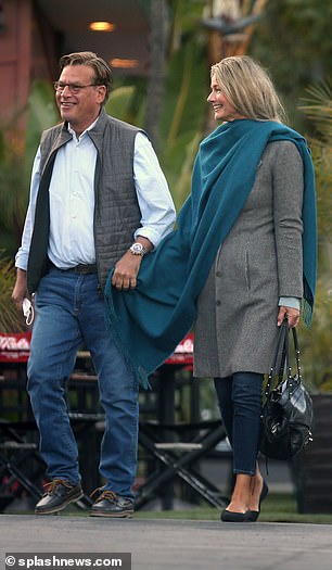 Dressed up: She stayed warm with multiple layers, including a long brown coat and a light blue sweater in addition to a teal pashmina draped across her shoulders