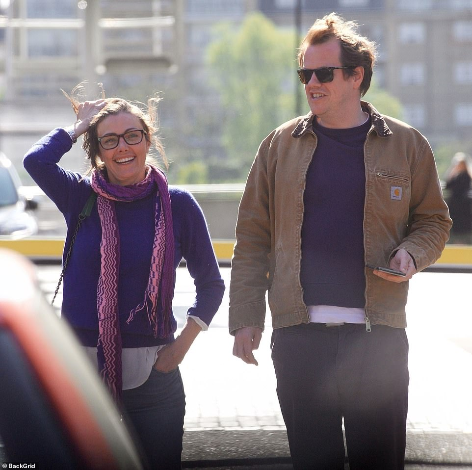 Tom Parker Bowles, 46, sports a pair of sunglasses as he walks alongside his female friend, who is seen brushing back her hair with one hand casually in her pocket, outside the exclusive River Café by the Thames in Hammersmith, west London