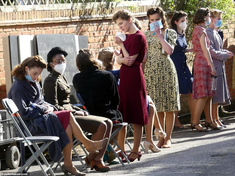 Wartime belles: Outside the pub, female extras were lined up dressed in a traditional tea dresses and t-strap shoes with their hair in vintage curls