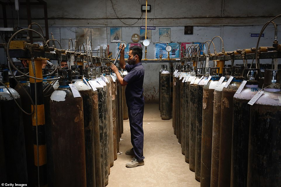 An employee fills oxygen cylinders inside an oxygen filling centre in Bengaluru, India